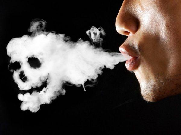 Мужчина выдыхает дым