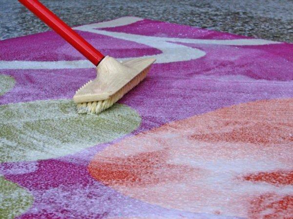 Чистят ковёр щёткой