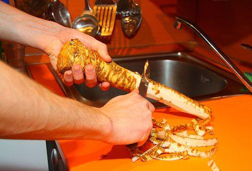 Ножом срезают ленточки кожуры с хрена