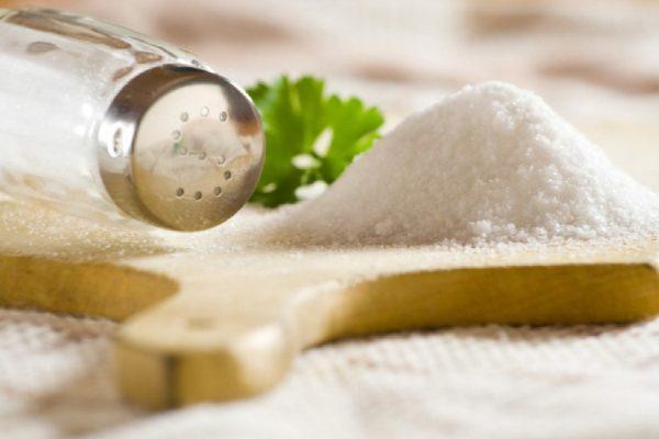 Солонка рядом с горкой соли