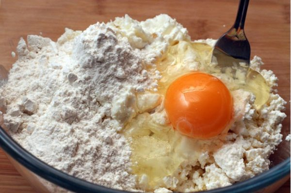 Творог, смешанный в миске с яйцом и мукой