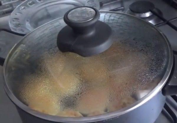 Сковорода с сырниками накрыта крышкой