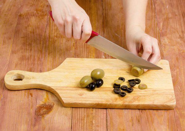 Маслины и оливки нарезают на доске
