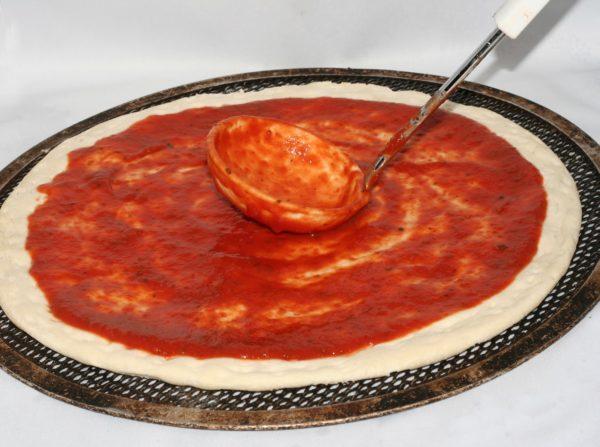 Тесто для пиццы смазывают томатным соусом