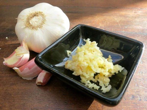 Целая головка чеснока и измельчённый чеснок в блюдце