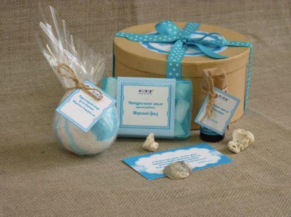Бомбочка и мыло голубого цвета ручной работы рядом с круглой бежевой коробкой с голубой лентой