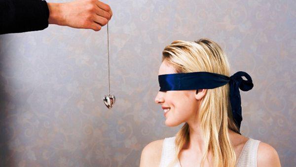 Цепочка с кулоном в виде сердца перед девушкой с завязанными глазами