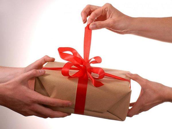 Девушка развязывает красную ленту на подарке, который держит мужчина
