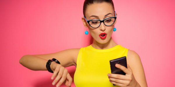 Девушка в жёлтой футболке и стильных очках смотрит на телефон, приподняв руку с часами