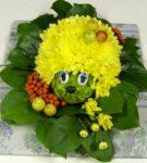 Ёжик из жёлтых цветов на зелёных листьях