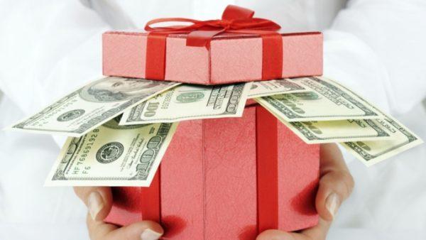 Из розовой коробки с красной лентой выглядывают стодолларовые купюры
