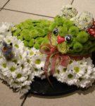 Кошка из зелёных цветов лежит в корзине на белых ромашках