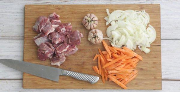 Чеснок и нарезанные мясо, лук, морковь
