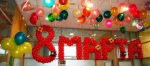 Под потолком красными воздушными шариками написано 8 марта