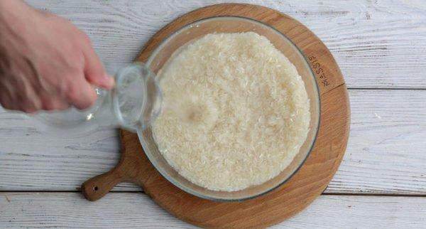 Рис и вода в миске на доске