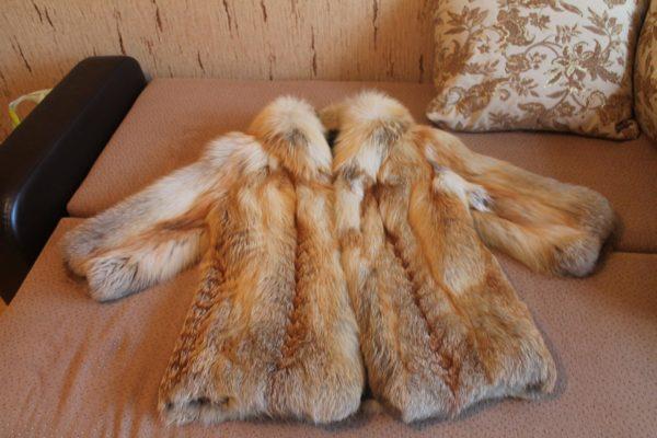 Шуба из лисы лежит на диване