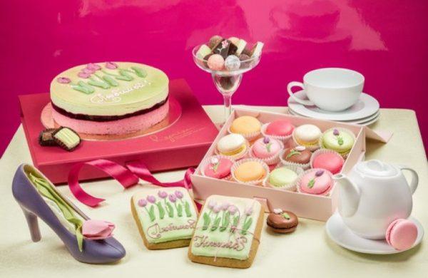 Торт, пирожное в виде туфельки, пряники на столе с белой чашкой и белым заварником