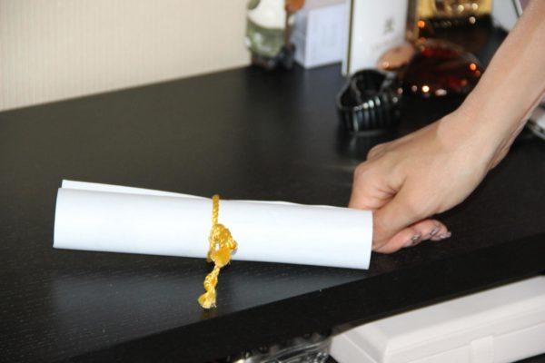 Женская рука возле свёрнутого листа бумаги, перевязанного жёлтой верёвкой