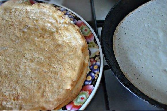 Блины в тарелке и тесто в сковороде
