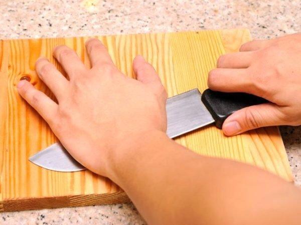Рука прижимает нож к разделочной доске