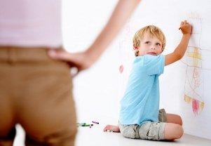 Мальчик. рисующий на стене цветными ручками