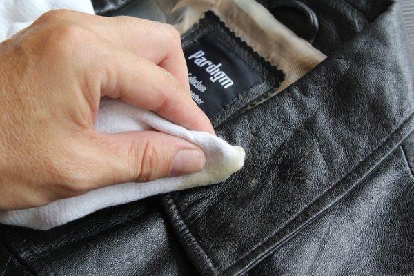 Белой тряпкой оттирают воротник чёрного кожаного пальто