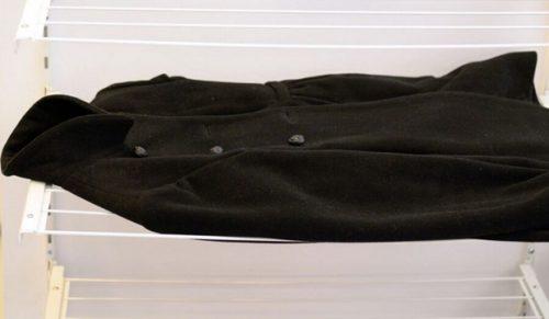 Чёрное пальто сушится горизонтально на сушке