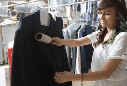 Девушка валиком чистит пальто, висящее на вешалке