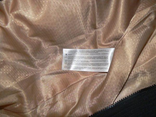 На бежевой подкладке кашемирового пальто ярлык с информацией по уходу