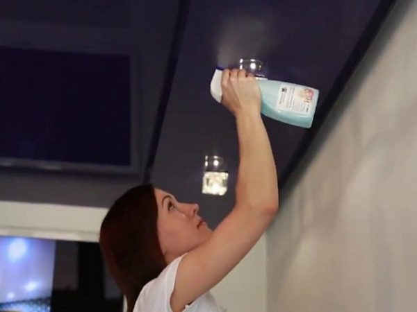 The girl uses a spray to clean stretch ceilings
