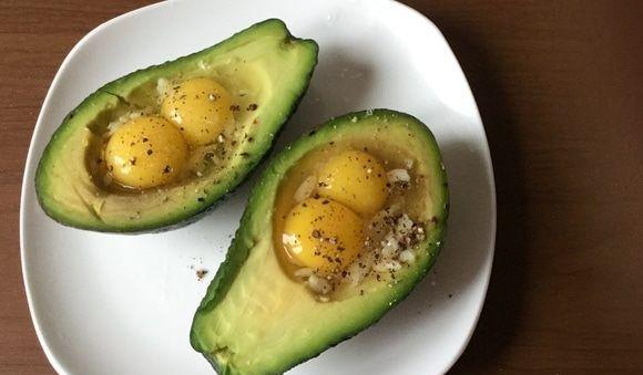 Половинки авокадо с начинкой из яиц на тарелке