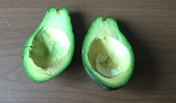 Половины плода авокадо на столе