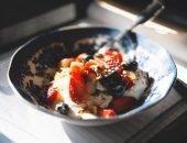 Йогурт с творогом и фруктами в тарелке
