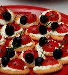 Закуска из крекеров с творожным сыром, черри и маслинами