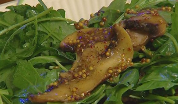 Листы руколы, обжаренные грибы и зёрна горчицы