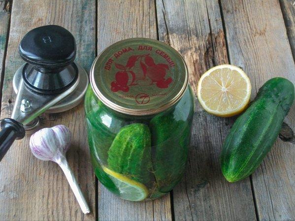 Маринованные огурцы в банке, закаточный ключ, головка чеснока и половина лимона