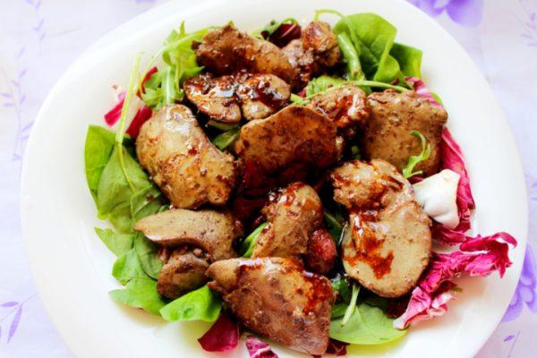Микс салатных листьев и обжаренная куриная печень в тарелке