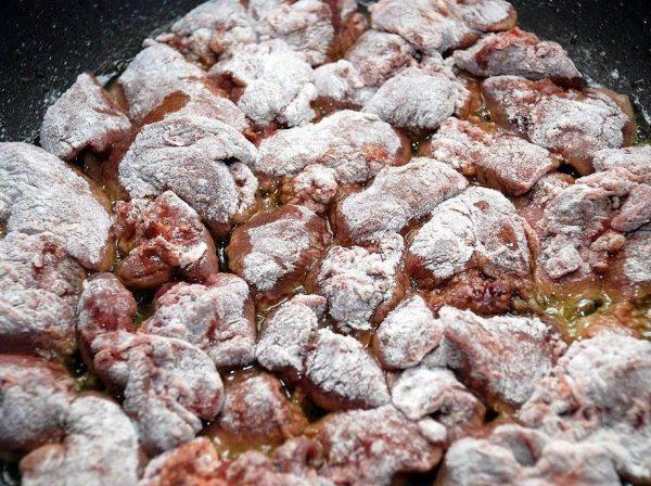 Обвалянная в пшеничной муке куриная печень в сковороде с горячим маслом