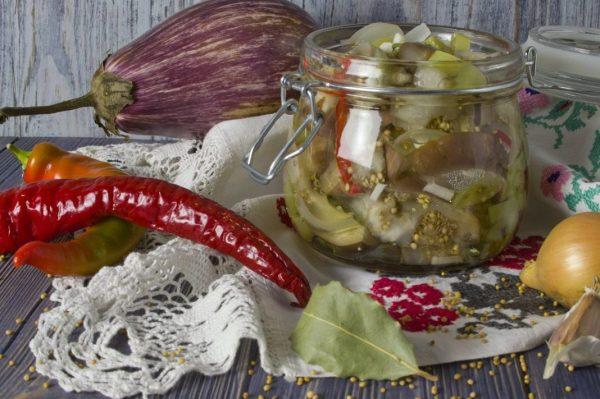 Заготовка из баклажан на столе, украшенном кружевной салфеткой, овощами и специями