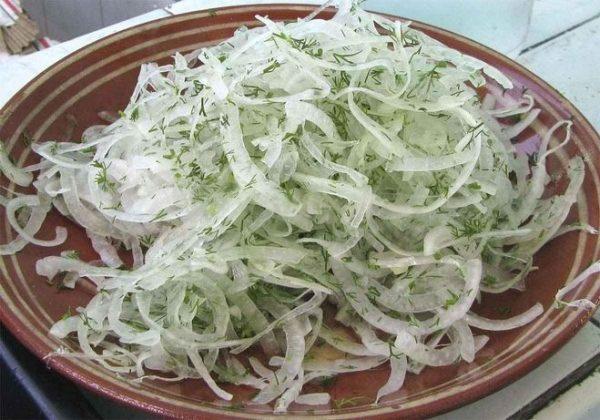 маринованный лук со свежим укропом на тарелке