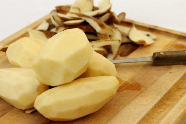 Очищенные клубни картофеля на разделочной доске