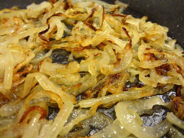 Обжаренный полукольцами репчатый лук в сковороде