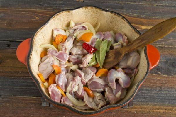 Свежие овощи и кусочки сырых куриных желудков в жаровне