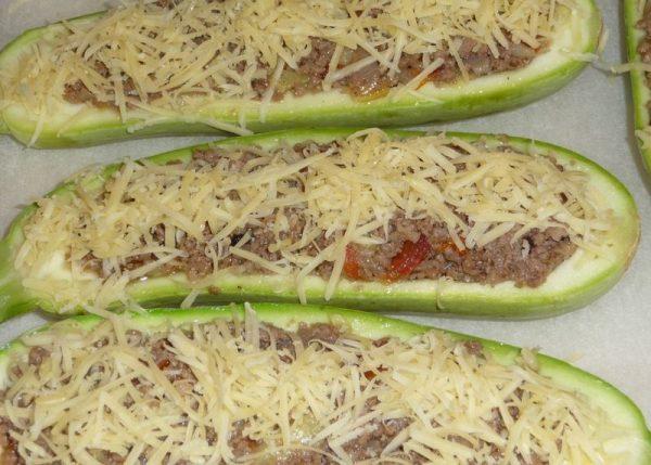 Заготовки из кабачков с фаршем, посыпанные тёртым сыром