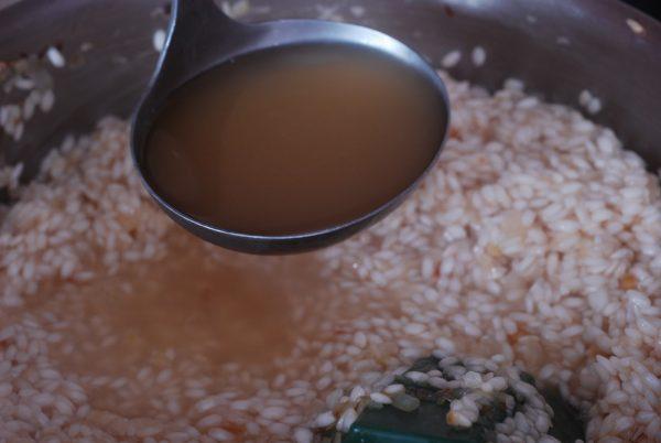 половник с бульоном над сковородой с рисом