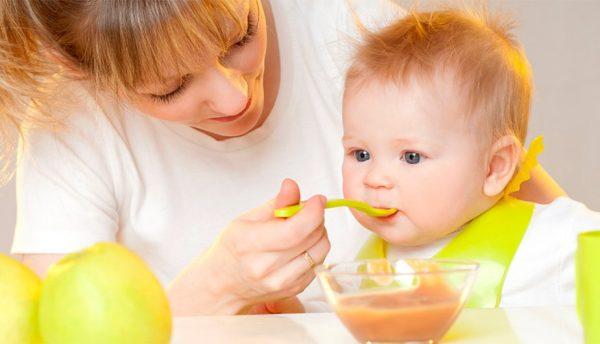 Мама кормит ребёнка с ложки