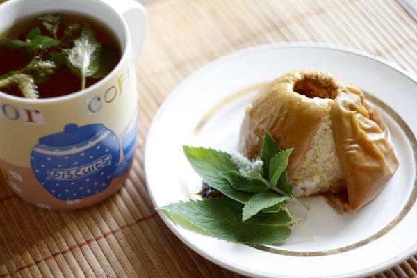 Печёное яблоко на тарелке рядом с чашкой чая