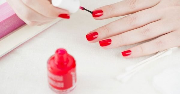 Женщина красит ногти на руках