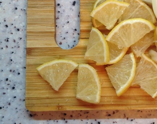 Нарезанный на кусочки лимон на разделочной доске