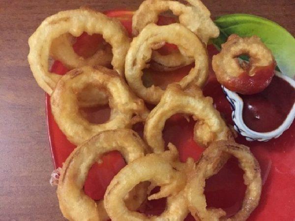 луковые кольца на блюде с соусом
